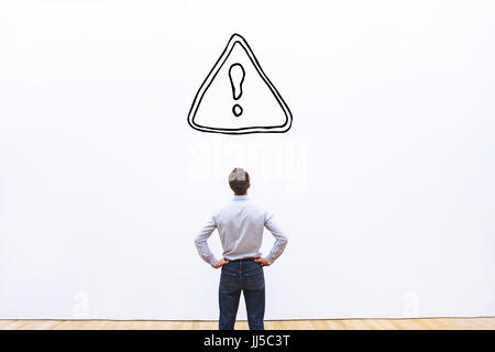 restrictions or alert concept in business, businessman looking at danger sign on white background - Stock Photo