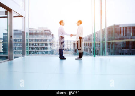 business cooperation concept, collaboration, two business people shaking hands in office interior - Stock Photo