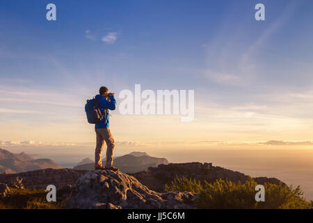 nature photographer traveler taking photo of beautiful landscape from top of the mountain - Stock Photo