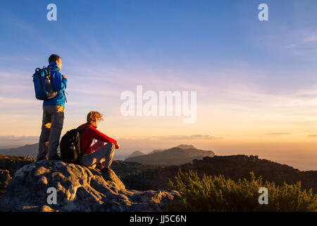 couple of hikers with backpacks enjoying panoramic view of sunset in mountains, travel and outdoor adventure concept - Stock Photo