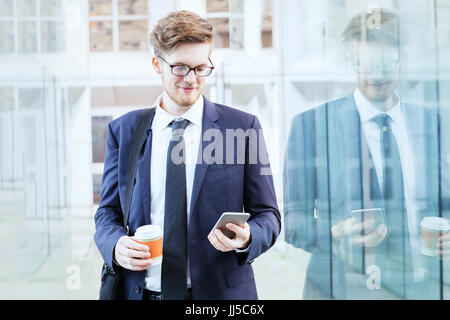 businessman using smartphone and drinking coffee in modern bright interior of office glass corridor - Stock Photo