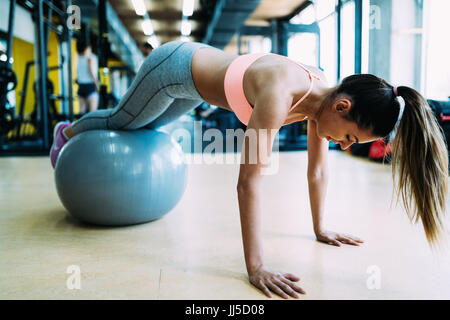 Fitness woman working push ups in gym - Stock Photo