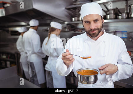 Attentive chef tasting food from spoon in kitchen at restaurant - Stock Photo