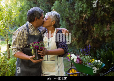 Romantic senior couple kissing each other in garden - Stock Photo