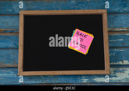 Close-up of back to school text written on sticky note - Stock Photo