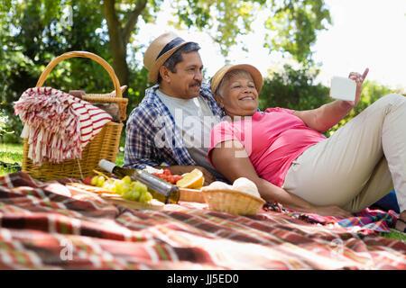 Senior couple relaxing in garden on a sunny day - Stock Photo