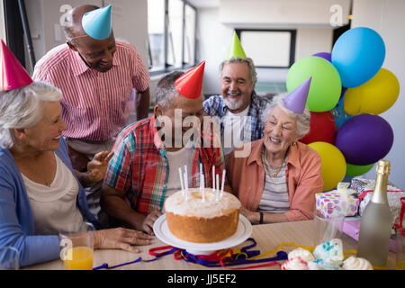 Happy senior friends by birthday cake celebrating at party in nursing home - Stock Photo