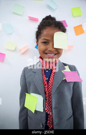 Happy businesswoman with sticky notes stuck on suit and head standing against wall - Stock Photo
