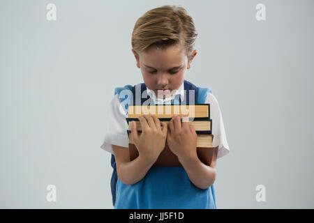 Close-up of schoolboy holding books against white background - Stock Photo