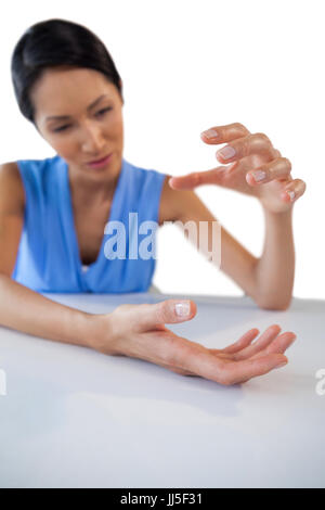 Young businesswoman gesturing while holding something at table against white background - Stock Photo