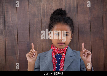 Portrait of girl pretending as businesswoman pointing upwards while standing against white background - Stock Photo
