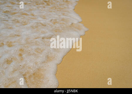 Closeup of sea foam from a wave on the beach. - Stock Photo