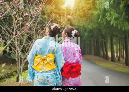 Travel tourist women standing watching cherry-blossom at sakura park, japan. Asian girlfriends looking at pink flowers - Stock Photo