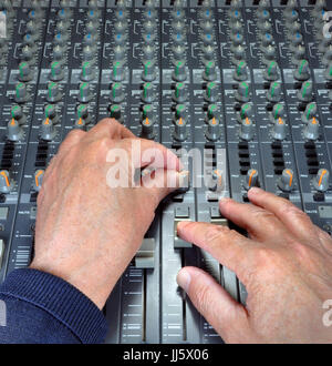 Experienced hands operating the faders, buttons and knobs on an analogue music mixing and recording desk in a studio - Stock Photo