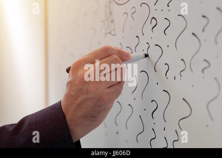Businessman sketching many question marks on office whiteboard, uncertainty and unpredictability in business - Stock Photo