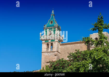 Beautiful view. Tower of the Monastery of Valldemossa in the Sierra de Tramuntana Mountains with park. - Stock Photo