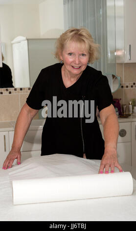 Masseuse preparing the client bed with a paper roll - Stock Photo