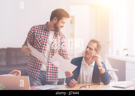Positive colleagues helping each other in the office - Stock Photo