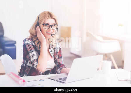 Cheerful call center operator sittign in the office - Stock Photo