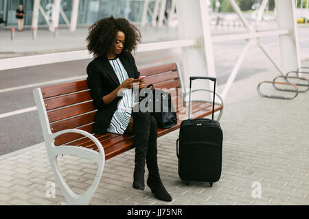 The stylishly dressed afro-a,erican traveler is sitting on the bench and chatting via the mobile phone. - Stock Photo