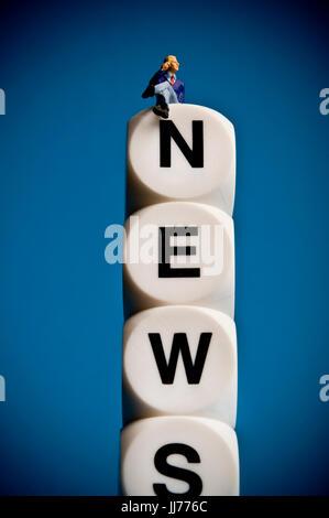 miniature figurine sitting on dice with word NEWS - Stock Photo