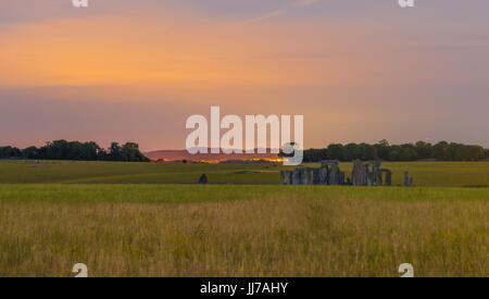 Stonehenge in Wiltshire, England. Take at night you can see a little of the light pollution behind in nearby Larkhill, - Stock Photo
