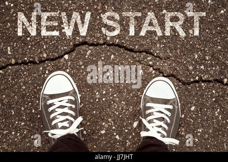 Man standing on cracked asphalt with NEW START sign - Stock Photo