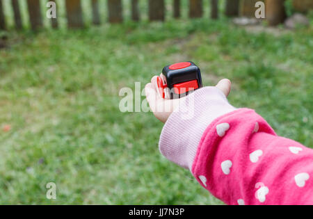 Little blonde girl holding a fidget cube stress relieving object, outdoors while playing in the middle of nature - Stock Photo