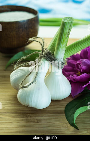 Young garlic bulbs tied up together with packthread on cutting board near bowl full of salt and pink peony flower. - Stock Photo
