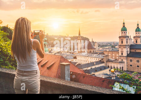 Tourist taking a photo with mobile of beatiful sunset in Salzburg Austria - Stock Photo