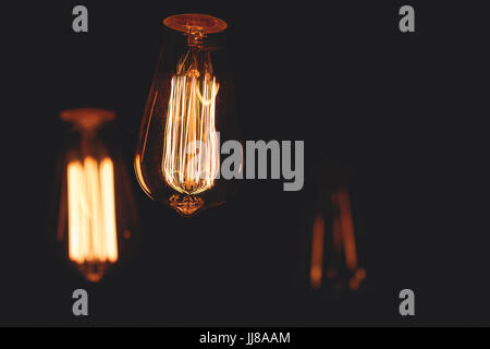 Close-up of glowing retro light bulbs on a black background. - Stock Photo