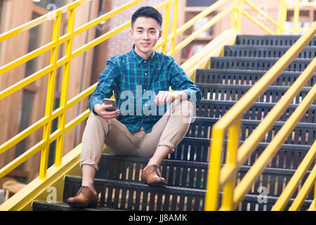 Young man on the stairs - Stock Photo