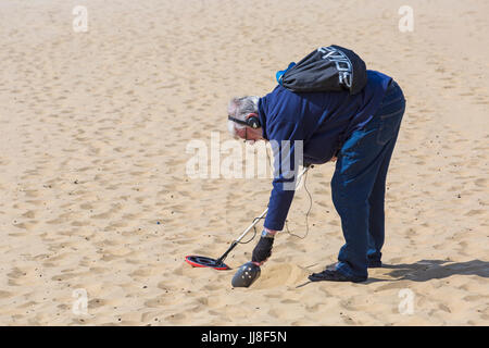 Treasure Hunter, man with metal detector looking for treasure at Bournemouth beach, Bournemouth, Dorset UK in July - Stock Photo