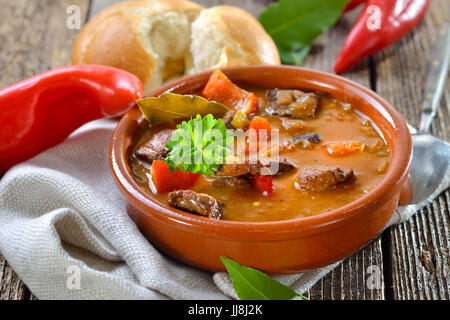 Hot Hungarian goulash soup served in a ceramic bowl with a fresh roll - Stock Photo