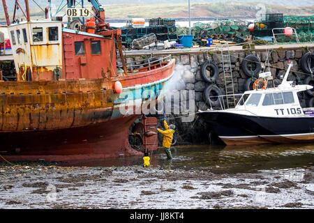 Dock scene, man pressure washing, a rusty, old fishing trawler, in Tobermory Harbour, Isle of Mull, Scotland. - Stock Photo