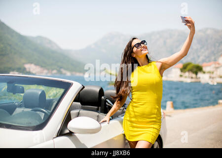 Pretty young woman in yellow dress taking selfie with mobile phone by white cabriolet car - Stock Photo