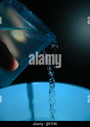 Water being poured out of a pale blue glass with black background - frozen in motion - Stock Photo