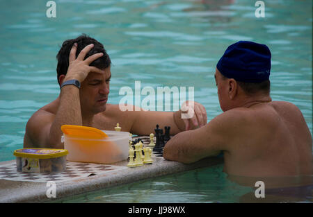 Two men play chess at a local spa in City Park, Budapest, hungary - Stock Photo