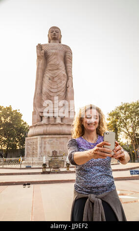 A woman taking a self portrait of herself in front of Thai Buddha Vihar in Sarnath, India. - Stock Photo