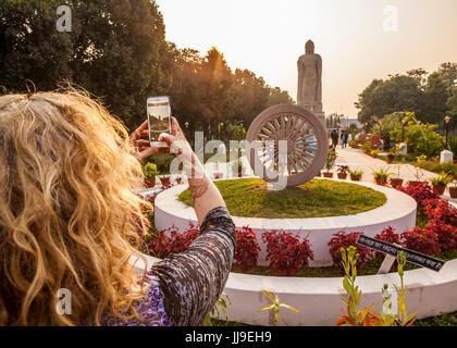 A tourist taking a cellphone picture of Thai Buddha Vihar in Sarnath, India. - Stock Photo