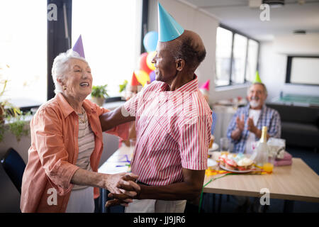 Senior couple wearing party hats dancing at birthday party in nursing home