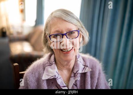 Portrait of cheerful senior woman wearing eyeglasses at nursing home - Stock Photo