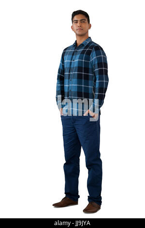 Full length portrait of confident young man with hands in pockets against white background - Stock Photo