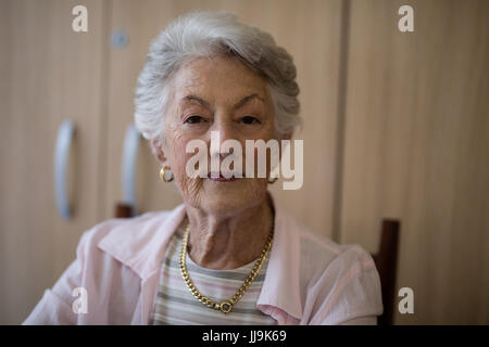Portrait of senior woman sitting on chair at nursing home - Stock Photo