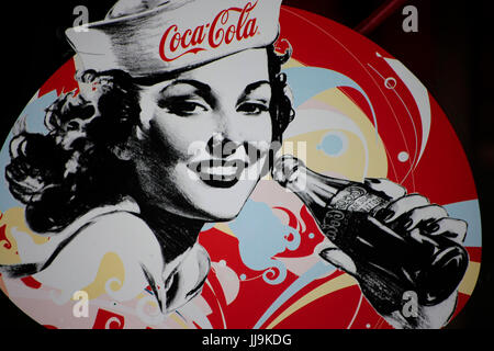 Coca Cola poster with woman in navy cap drinking from bottle - Stock Photo