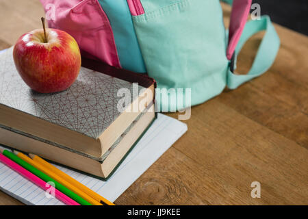 Close-up of apple on stack of books with schoolbag - Stock Photo