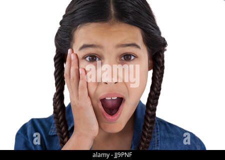 Portrait of cute girl surprised against white background - Stock Photo