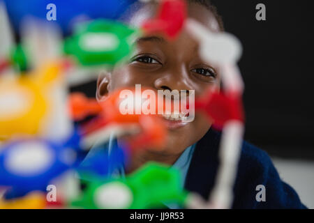 Portrait of schoolgirl experimenting molecule model against black background - Stock Photo