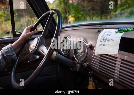 A driver has one hand on the steering wheel of an antique Chevrolet pickup truck with a to-do list on the dashboard. - Stock Photo