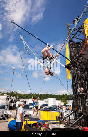 A young woman does a flip mid-air during pre-race activities set up at the New Hampshire 301 NASCAR Sprint Cup - Stock Photo
